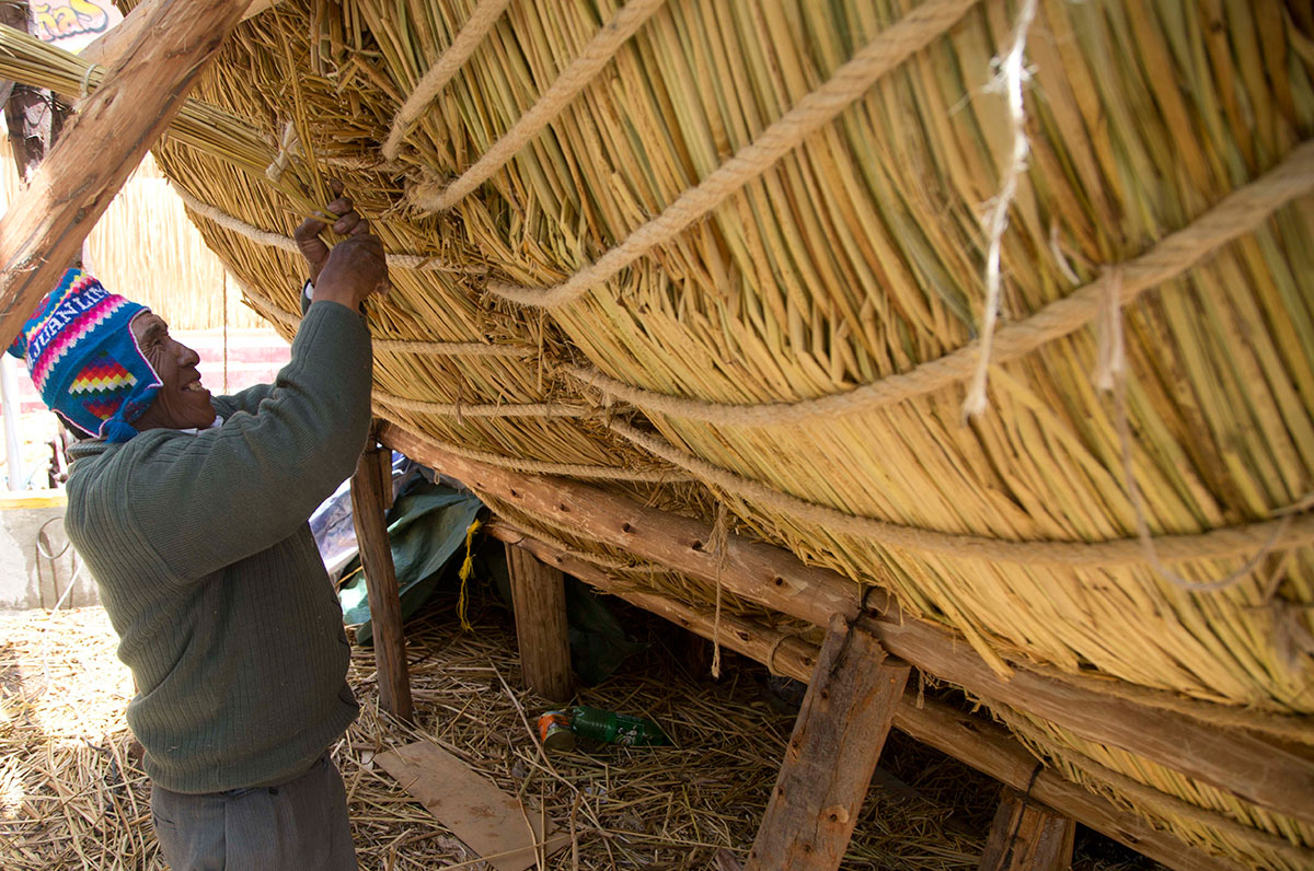 "Seventy-one-year-old Juan Limachi, who has been building reed boats since the age of seven using the technology inherited from his Aymara ancestors, works on the ""Viracocha III,"" in La Paz, Bolivia, Wednesday, Oct. 19, 2016. (Juan Karita/AP)"