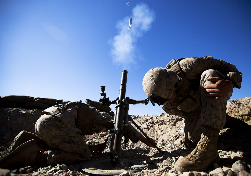 U.S. Marine Corps Lance Cpl. Justin Downing and Lance Cpl. Patrick Walker, mortar men with the 3rd Battalion, 3rd Marine Regiment, brace themselves while firing a 60mm mortar round during Exercise Clear, Hold, Build 3 on Marine Corps Air Ground Combat Center Twentynine Palms, Calif., Sept. 21, 2011. (DoD photo by Cpl. Reece Lodder, U.S. Marine Corps/Released)