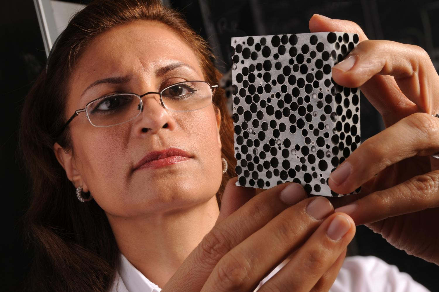 Afsaneh Rabiei examines a sample of metal foam. A new study by Rabiei finds that novel light-weight composite metal foams are significantly more effective at insulating against high heat than the conventional base metals and alloys that they're made of, such as steel. The finding means the CMF is especially promising for use in storing and transporting nuclear material, hazardous materials, explosives and other heat-sensitive materials, as well as for space exploration. (North Carolina State University)